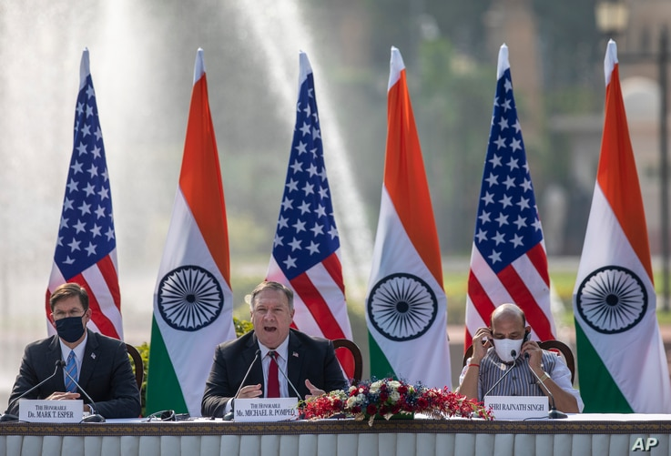 U.S. Secretary of State Mike Pompeo, center, speaks as Secretary of Defence Mark Esper, left, and Indian Defence Minister Rajnath Singh sit beside him during a joint press conference at Hyderabad House in New Delhi, India, Oct. 27, 2020.