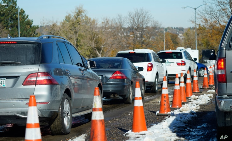 A long line of motorists wait at a drive-in COVID-19 testing site Tuesday, Oct. 27, 2020, in Federal Heights, Colo. Denver will…