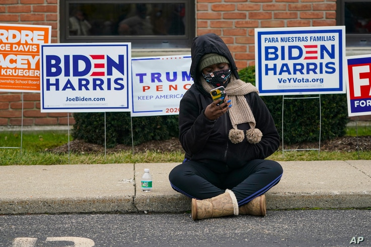 A voter sits on the sidewalk as voters wait in long lines to cast their ballots during early voting at St. Luke's United…