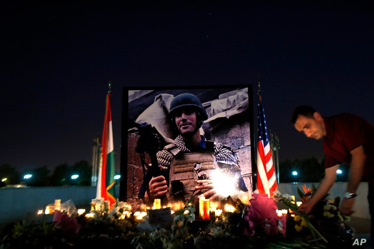 A man lays flowers next to a photograph of James Foley, the freelance journalist killed by the IS group, during a memorial service in Irbil, 350 kilometers (220 miles) north of Baghdad, Iraq, Aug.t 24, 2014.
