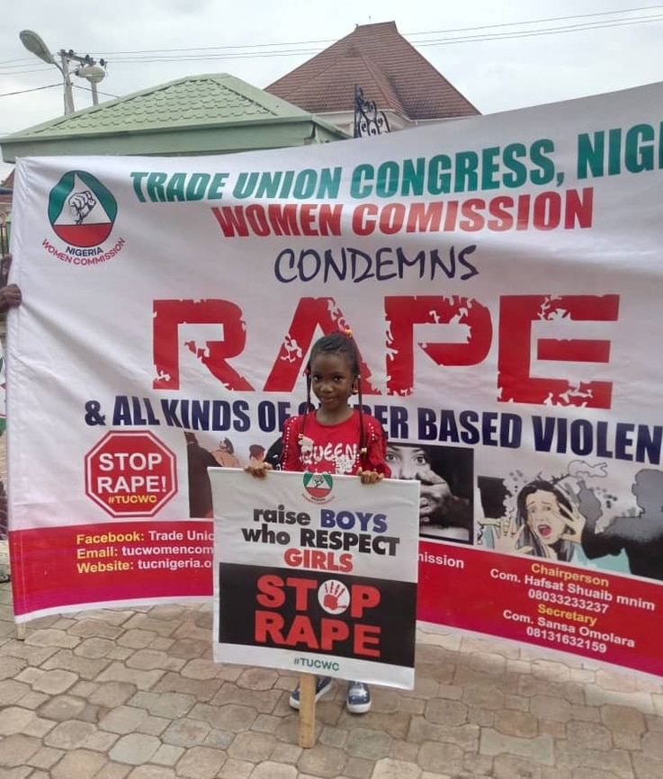 A young girl holds a sign that says 'Raise Boys Who Respect Girls: Stop Rape.' She stands in front a huge anti-rape banner of the Women Commission of the Nigeria Trade Union Congress.