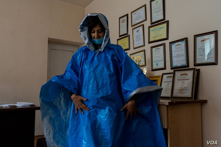 Jasmine Khachatryan, who heads a kindergarten that is now being used as a temporary shelter, wears a homemade poncho volunteers made to donate to soldiers on Oct. 8, 2020 in Goris, Armenia. (Yan Boechat/VOA)