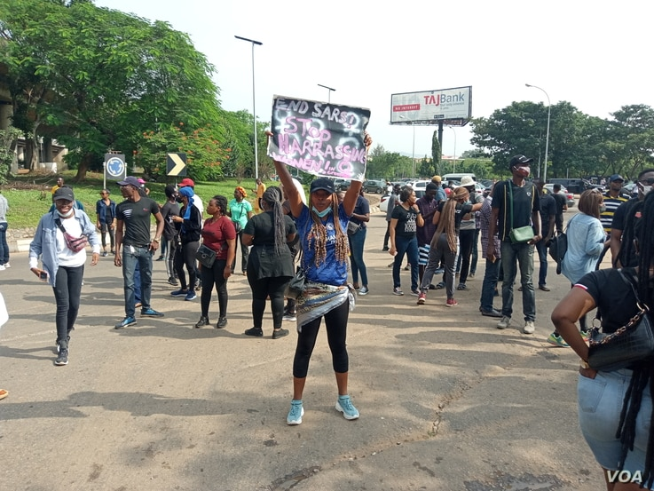 """A female protester holds up a placard reading """"End SARS"""" during continued protests at the popular Berger junction in Abuja, Oct. 14, 2020."""