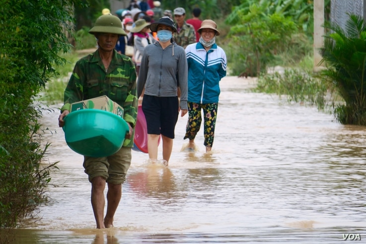 Locals walking through a flooded road in Quang Tri.