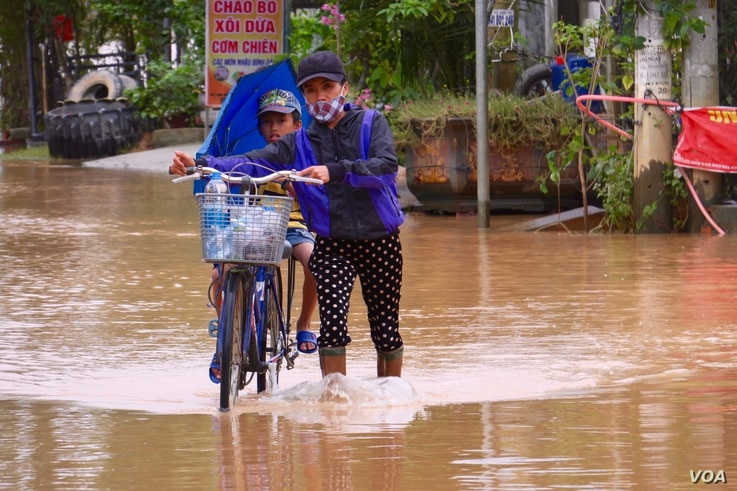 A woman pushes a child on a bicycle through a flooded street in Quang Tri.