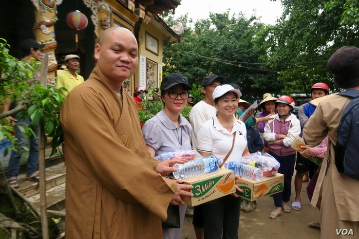 A monk hands out food supplies to locals in a pagoda in Quang Tri.