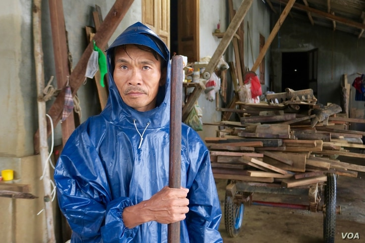 A local man wearing a raincoat stands near a home that was recently flooded in Quang Tri.