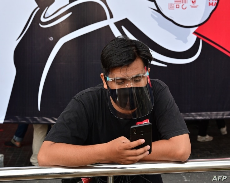 A journalist wearing a face mask and shield stands in front of a banner encouraging people to wear face masks during a campaign…
