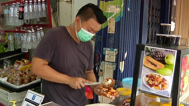 Ben Lim prepares his family fruit shop's popular rojak salad. Lim says business is down almost 40-percent in just the past week. (David Grunebaum/VOA)