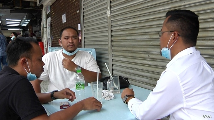 Hakimi Azri (pictured in the middle) enjoyed lunch outside with some friends. Azri says he usually goes straight home from work each day because of the rising number of Covid-19 cases. (David Grunebaum/VOA)
