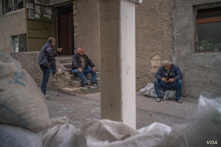 Men sit outside an underground shelter before bombs and sirens go off in Nagorno-Karabakh, Oct. 9, 2020. (Yan Boechat/VOA)