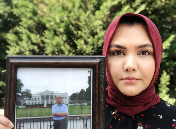 Subi Mamat Yuksel holds a photo of her father, Mamat Abdulla, in Virginia in April. (Photo courtesy: Subi Mamat Yuksel)