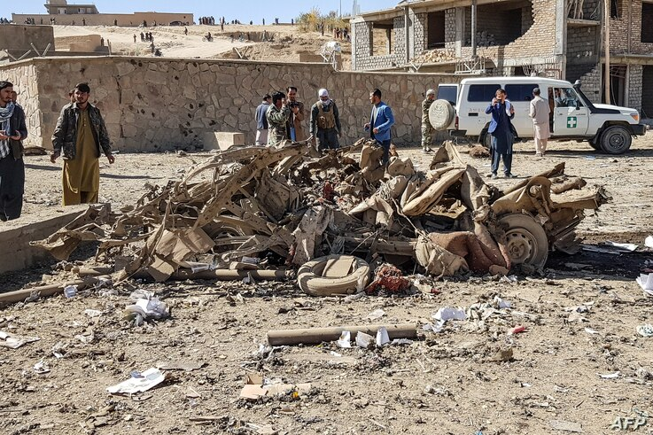 Security personnel and residents gather around the site of a car bomb attack that targeted an Afghan police headquarters in Feroz Koh, the capital of Ghor Province, Oct. 18, 2020.