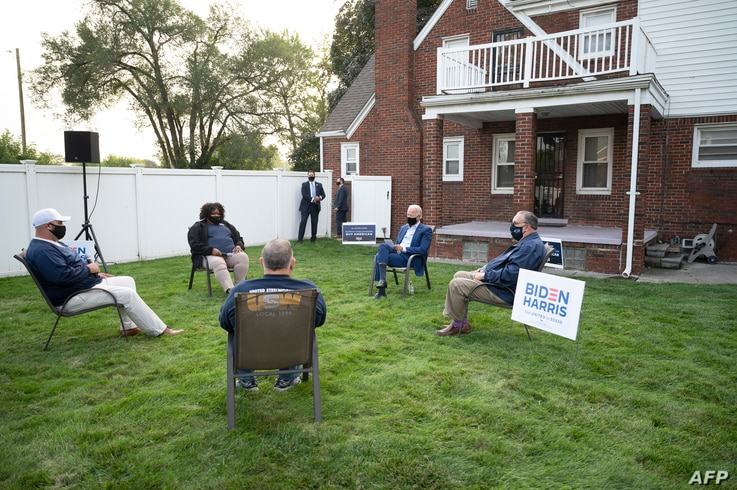 FILE - Democratic presidential candidate former Vice President Joe Biden (C) speaks with steelworkers during a backyard conversation in Detroit, Michigan, Sept. 9, 2020.