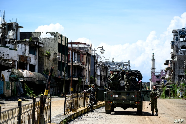 FILE - Soldiers are seen on truck among destroyed buildings in Marawi City, southern Philippines, May 23, 2019.