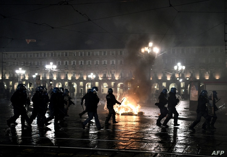 Police officers are seen in front of a garbage bin set on fire during a protest against new government restrictions to curb the spread of the coronavirus, in Turin, Italy, Oct. 26, 2020.