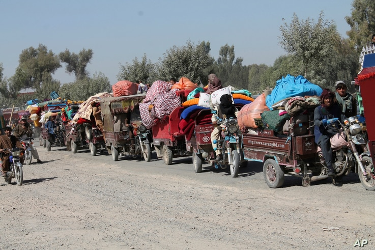 Afghan families leave their houses after fighting between the Afghan military and Taliban insurgents in Helmand province, southern of Afghanistan, Oct. 13, 2020.