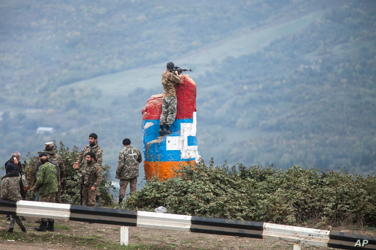 A sniper of Nagorno-Karabakh's militia observes the land ahead during a military conflict near Hadrut, the separatist region of Nagorno-Karabakh, Oct. 11, 2020.