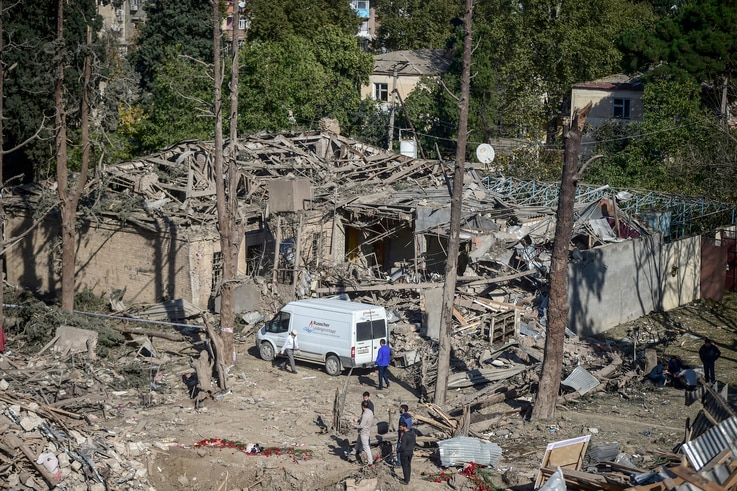 People look at the destroyed houses a day after shelling by Armenian's artillery during fighting over the separatist region of Nagorno-Karabakh, in Ganja, Azerbaijan, Oct. 12, 2020.