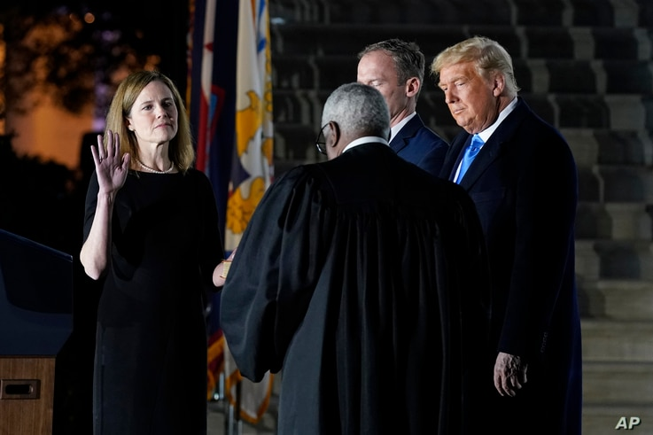 President Donald Trump watches as Supreme Court Justice Clarence Thomas administers the Constitutional Oath to Amy Coney Barrett on the South Lawn of the White House in Washington, Oct. 26, 2020, after Barrett was confirmed by the Senate earlier.