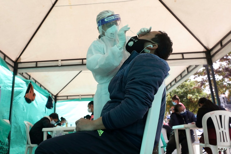 A health worker takes a nasal swab sample for a COVID-19 test, provided for free by the municipal government in Bogota, Colombia, Oct. 16, 2020.