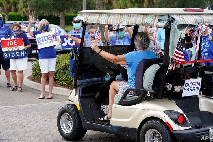 FILE - A voter arrives by golf cart for early voting as others wave signs, in The Villages, Florida, Oct. 7, 2020.