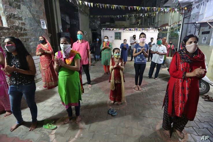 Indians, wearing face mask and maintaining physical distance, participate in religious rituals during Navratri or nine nights festival celebrations in Ahmedabad, Oct. 21, 2020.