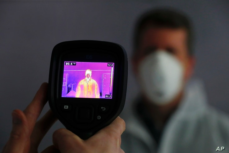 FILE - An infrared camera is shown scanning a person for elevated body temperature at a General Motors plant in Warren, Michigan, April 23, 2020.