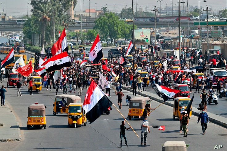 Demonstrators hold national flags as they head toward Tahrir Square for anti-government protests in Baghdad, Iraq, Oct, 1, 2020.