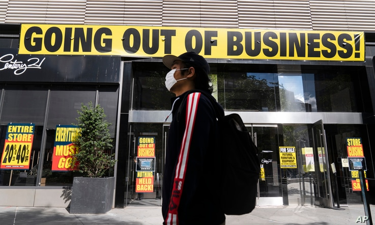 A man wearing a mask walks by Century 21 department store, Sept. 30, 2020 in the Brooklyn borough of New York.