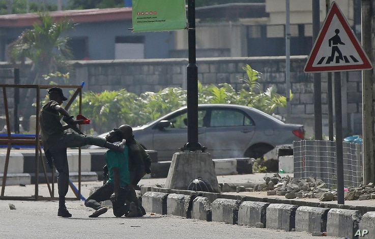Police officers detain a protester at the Lekki toll gate in Lagos, Nigeria.After 13 days of protests against alleged police brutality, authorities have imposed a 24-hour curfew in Lagos.