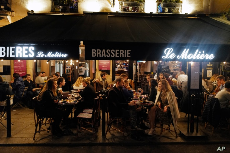 Parisians enjoy food and drink on a terrace of a restaurant before the nightly coronavirus comes into effect, in Paris, France, Oct. 23, 2020.
