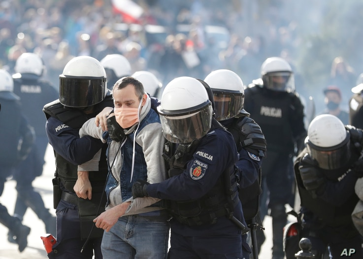 Polish police in riot gear detain protesters angry over new restrictions aimed at fighting the coronavirus pandemic, in Warsaw, Oct. 24, 2020.
