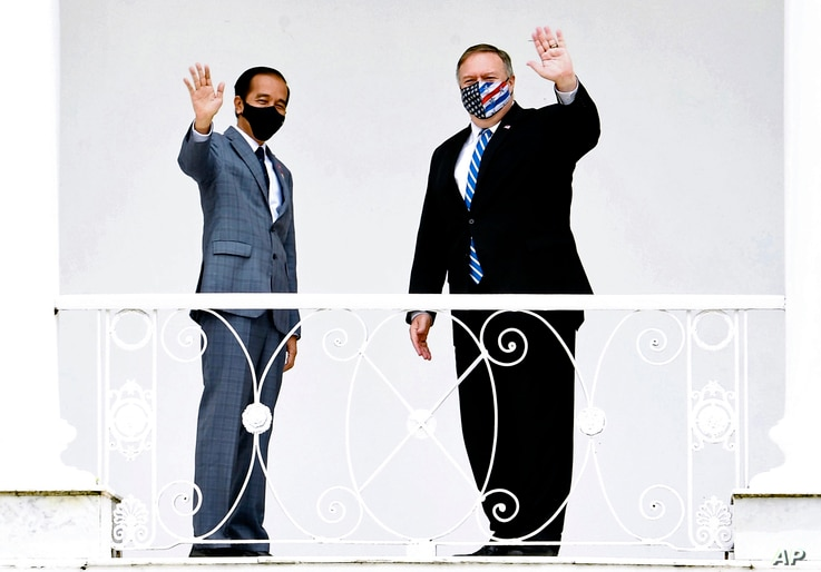 In this photo released by Indonesian Presidential Palace, Indonesian President Joko Widodo, left, and U.S. Secretary of State Mike Pompeo wave to photographers at Bogor Presidential Palace in Bogor, West Java, Indonesia, Oct. 29, 2020.