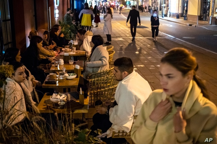 Customers sit outside a restaurant at Patriarshiye Prudy, a hip restaurant and bar district in Moscow, Russia, Oct. 16, 2020.