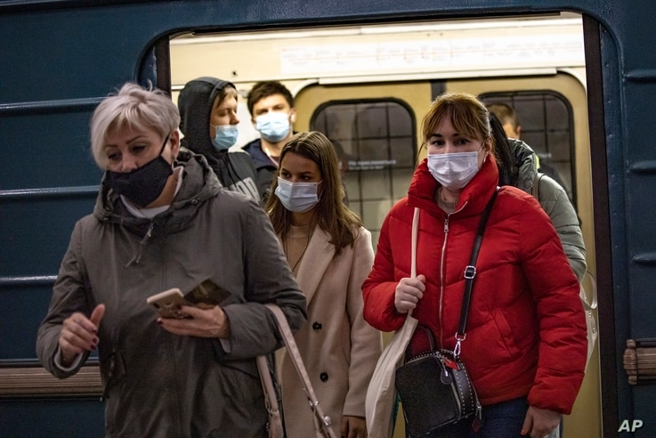People wearing face masks to protect against the coronavirus exit a subway car in Moscow, Russia, Oct. 19, 2020.