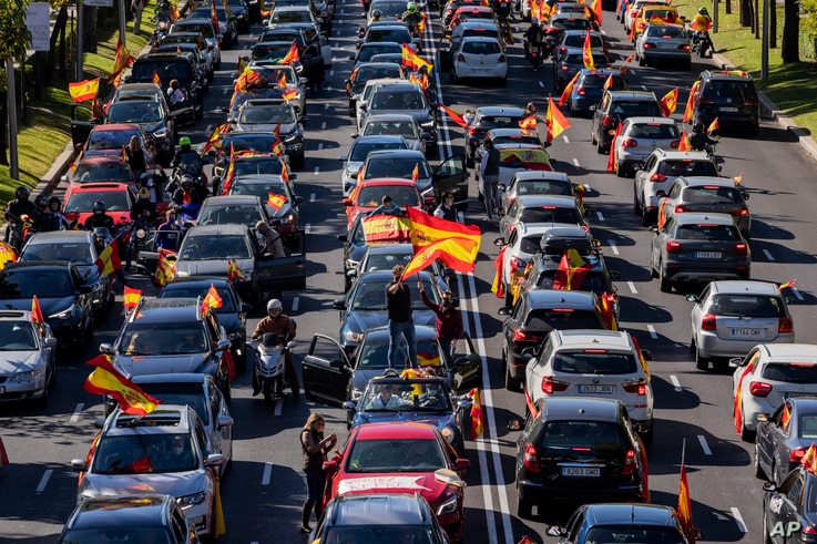 People wave Spanish flags during a drive-in protest organized by Spain's far-right Vox party against the government's handling of the nation's coronavirus outbreak in Madrid, Oct. 12, 2020.