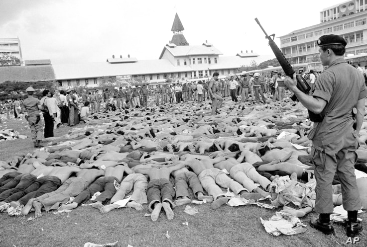 FILE - Police stand guard over Thai student protesters lying on a soccer field at Thammasat University, in Bangkok, Thailand, Oct. 6, 1976.