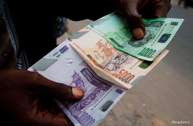 FILE - A trader displays Congolese currency bills on a street in Kinshasa, Democratic Republic of Congo, July 3, 2012.