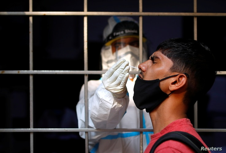 A man reacts as a health care worker collects a swab sample to test for the coronavirus, at a testing site, in New Delhi, India, Oct. 17, 2020.