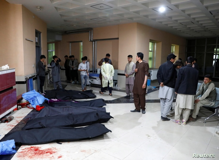Afghan men look for their relatives as body bags are laid out at a hospital, following a suicide bombing in Kabul, Afghanistan, Oct. 24, 2020.