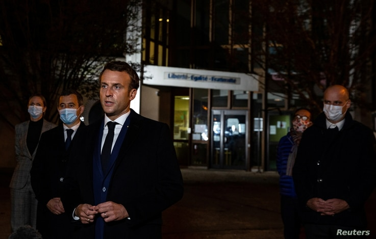 French President Emmanuel Macron, flanked by offcials, speaks to the press following a stabbing attack at a school in the Conflans-Sainte-Honorine suburb of Paris, France, Oct. 16, 2020.