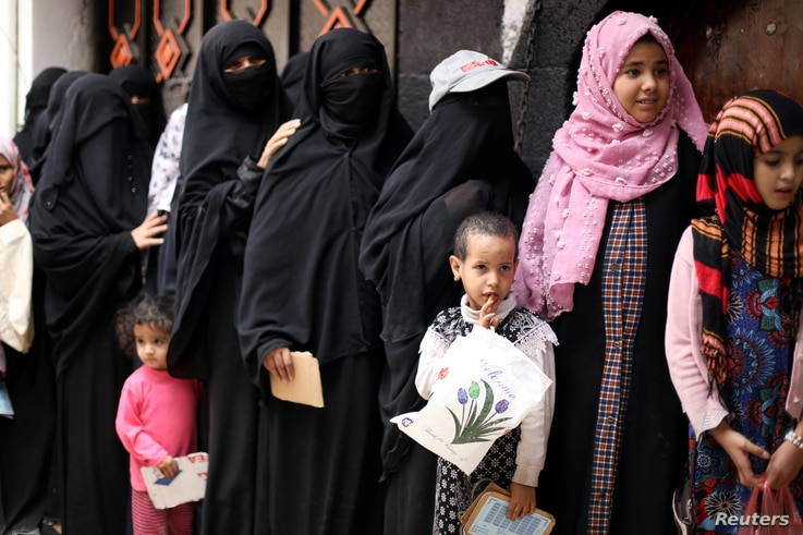 FILE - Women and children queue to receive food rations at a charity kitchen in Sanaa, Yemen, July 19, 2020.