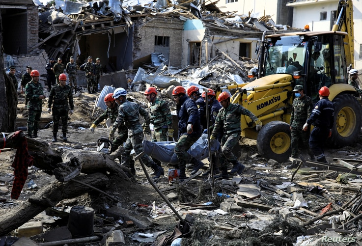 Search and rescue teams carry the body of a victim from the blast site hit by a rocket during the fighting over the breakaway region of Nagorno-Karabakh in the city of Ganja, Azerbaijan, Oct. 11, 2020.