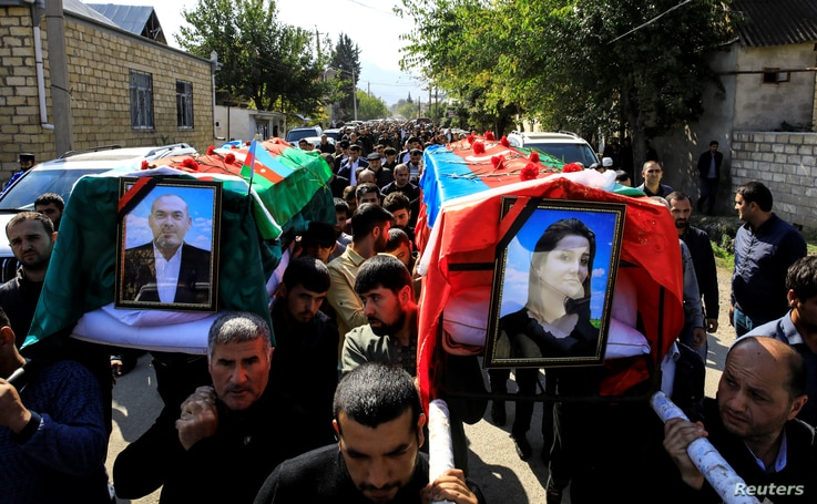 People carry the coffins of Anar Aliyev and his wife Nurcin Aliyeva, killed in Ganja attack during the fighting over the breakaway region of Nagorno-Karabakh, in the city of Shamkir, Azerbaijan, Oct. 12, 2020.