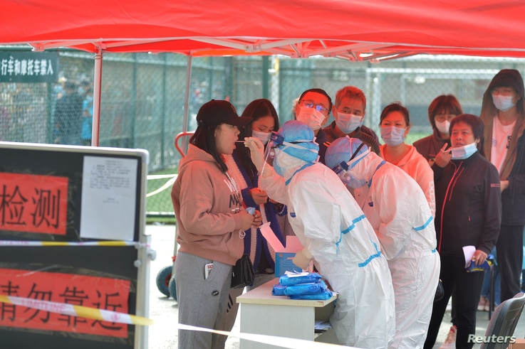 Medical workers in protective suits collect swabs for nucleic acid tests during a city-wide testing following COVID-19 cases in Qingdao, Shandong province, China, Oct. 12, 2020.