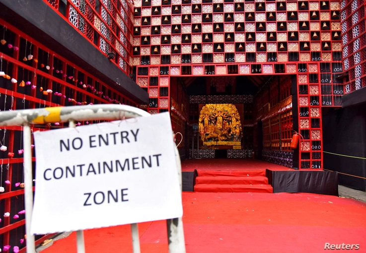 """A health notice hangs on railing of a closed """"pandal"""" or a temporary platform, on the first day of Durga Puja festival, amidst the spread of COVID-19 in Kolkata, India, Oct. 22, 2020."""