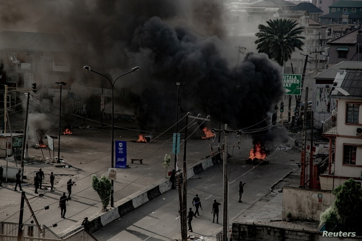Armed men are seen near burning tires on a street in Lagos, Nigeria Oct. 21, 2020, in this image obtained from social media.