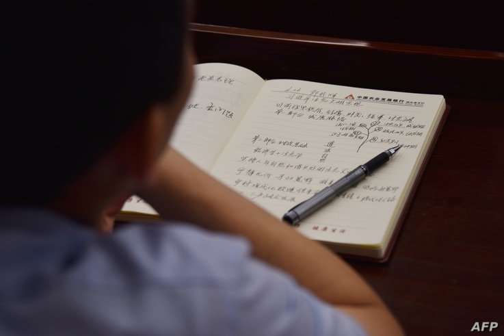 This photo taken on June 26, 2019 shows an adult student taking notes on Xi Jinping thought in a class at the Party School of…