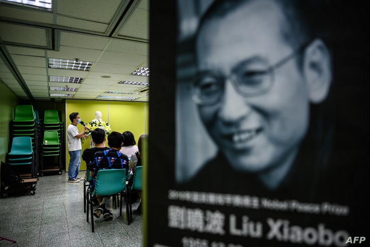 Activists hold a memorial event to mark the third anniversary of the death of Chinese dissident Liu Xiaobo (pictured R), in…